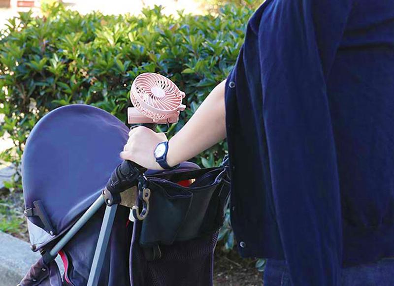 ミニ扇風機をベビーカーのハンドルに取り付けている女性