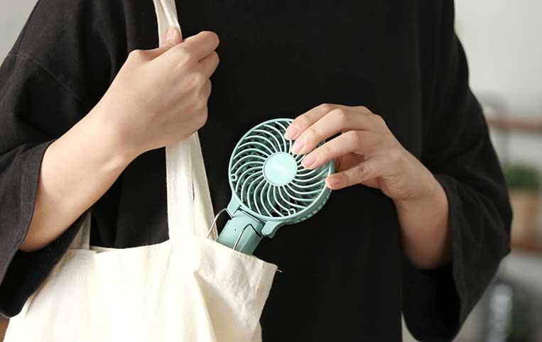 ミニ扇風機をバッグに入れている女性