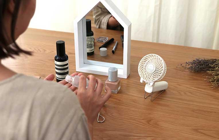 メイク中にミニ扇風機を使っている女性